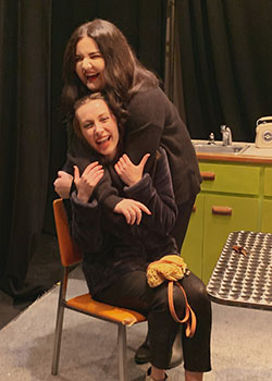 Image of actress standing behind, and hugging, another actress who is sitting down