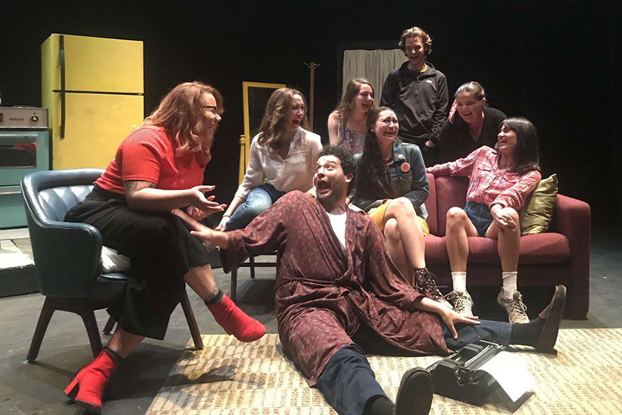 Image of actors on stage in an apartment setting, laughing and looking at each other on a couch