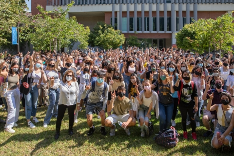 Hundreds of students stand in the meditation garden in front of the Contemporary Arts Center.