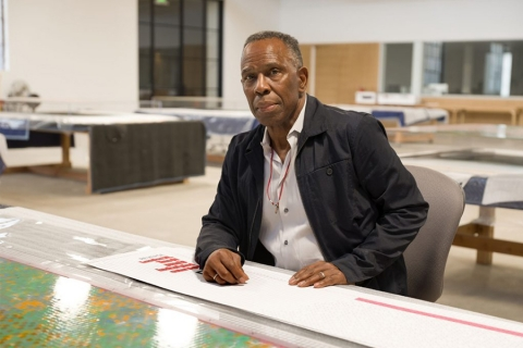 Black man seated behind what appears to be a drafting table; large-scale art-prints, or perhaps maps, displayed