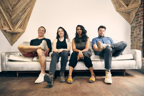Four people sitting on couch in a room with brick and wood accents on walls