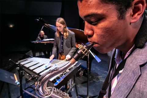 Image of saxophone player in foreground; xylophone player behind; Kei Akagi at piano in background