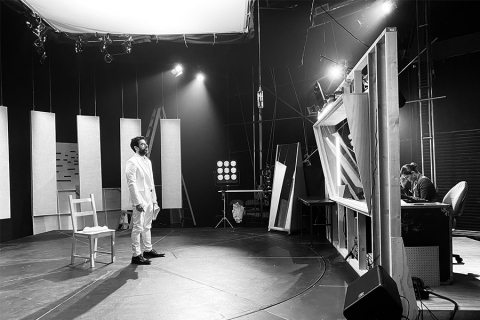 Man in white under lights of a sound studio, a technician on the other side of a glass partition