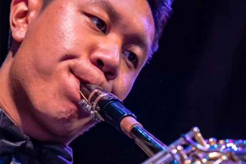Closeup of musician with lips to reeded instrument