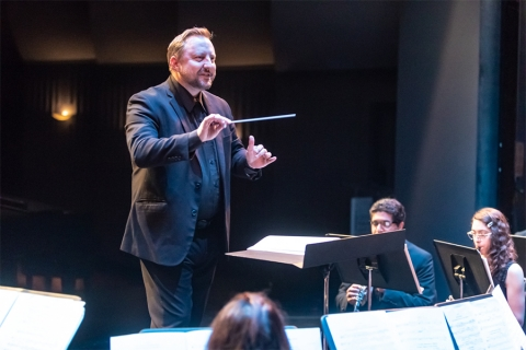 Image of music conductor with baton in hand, gesturing to students with music stands in front of them holding sheet music