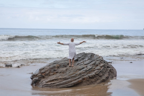 Image of bald person in tunic-like garment, standing with arms outstretched, back to camera, on a large rock on a beach with crashing waves